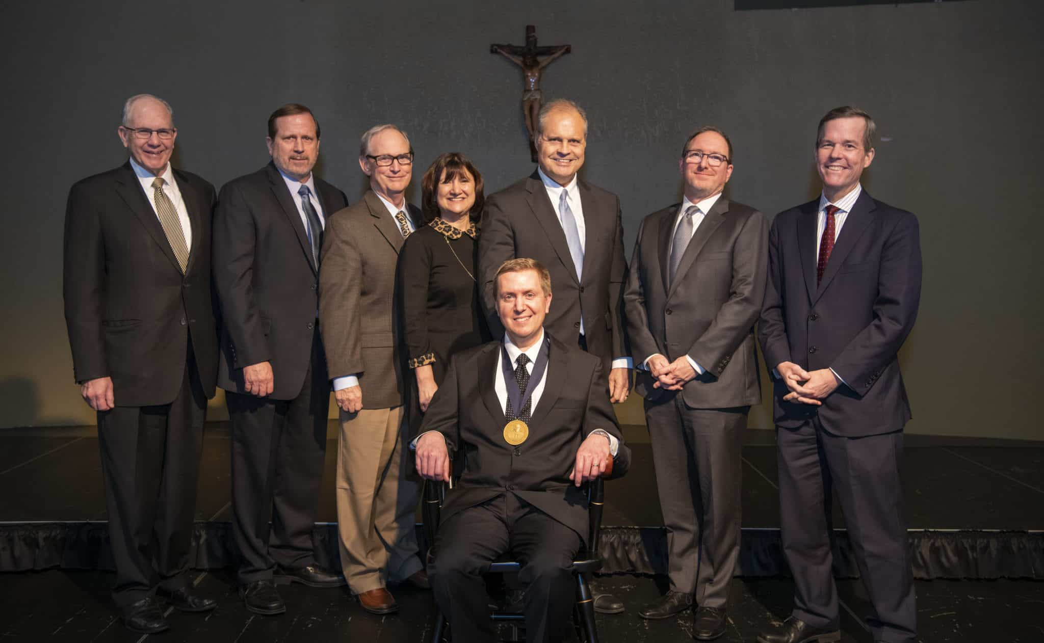 Scott Dickson, M.D. (seated) was invested Feb. 6 in the chair, which is awarded on a three-year, rotating basis.