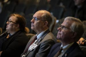 Christopher T. Westfall, M.D., (center) executive vice chancellor and dean of the College of Medicine, and Steppe Mette, M.D., senior vice chancellor for UAMS Health and chief executive officer of the Medical Center, listen intently to the State of the University address.