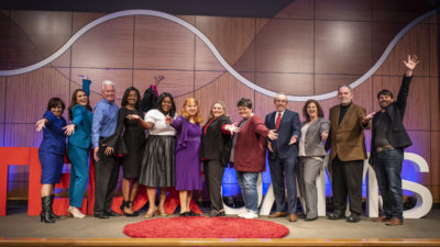 The 10 TEDxUAMS presenters and some of team that put on the event celebrate on stage at the end of the day.