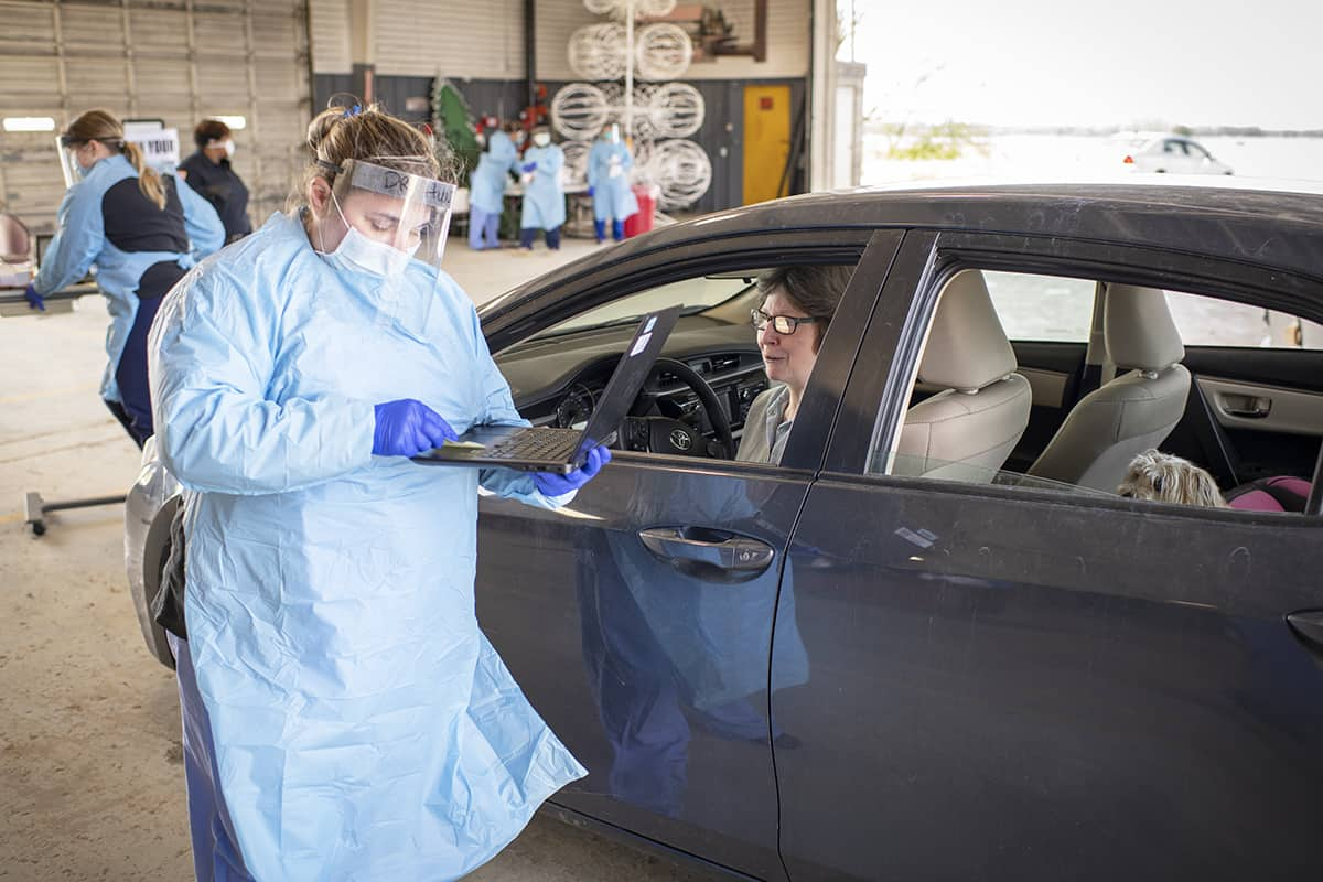 Jennifer Hunt, M.D., left, screens a patient for COVID-19 during a UAMS-led drive-through screening in Helena.