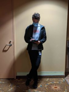 Leland Turner, College of Pharmacy class of 2014, leans against a wall while wearing a face mask.