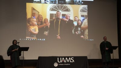 Student being hooded with family