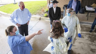 Jennifer Hunt, left, points toward the entryway for the drive-thru while describing the flow of traffic to Gov. Asa Hutchinson, second from left, and UAMS Chancellor Cam Patterson (wearing black cap).