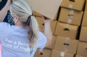 A UAMS volunteer unloads food boxes.