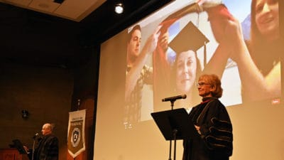Melanie Reinhardt, Pharm.D., right, and Eddie Dunn, Pharm.D., left, read out the names of College of Pharmacy graduates as each is hooded on live video June 13 at the college's Honors Convocation.