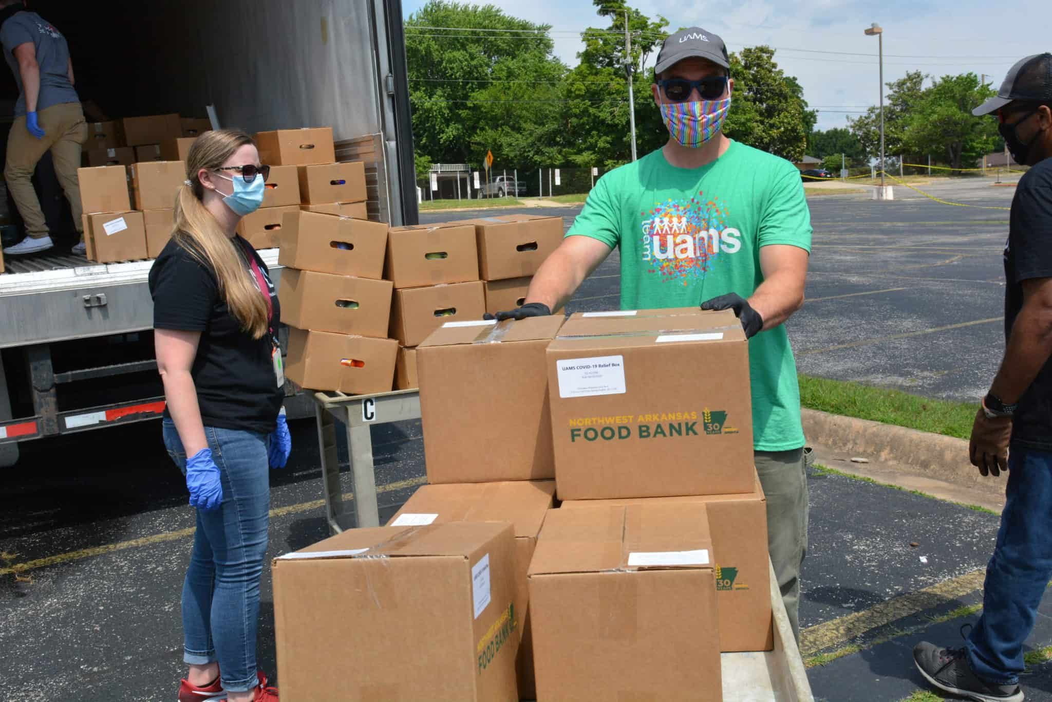 Peter Cooper of UAMS Northwest unloads a truck of food relief boxes.
