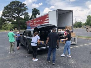 UAMS straff and students load up a car for food delivery.