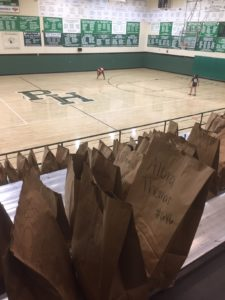 UAMS Day Camp attendees spend time in the Pulaski Heights Middle School gym while bags containing the personal items of the school's regular students who had to leave the school unexpectedly in March await being collected by those students' parents.