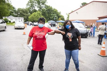 Practicing social distancing and masked, State Sen. Linda Chesterfield, left, and state Rep. Jamie Scott bump elbows shortly after the start of the testing drive-thru.