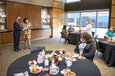 Pattie Shuffield, standing in white coat, takes a photo of MVP Gayla Houston with Chancellor Patterson at the MVP luncheon.