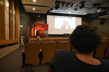 Presenters at the College of Pharmacy's Residency Graduation listen in the Smith Auditorium as keynote speaker, Kaitlin Bates, Pharm.D., as she uses a live video connection to address the audience.