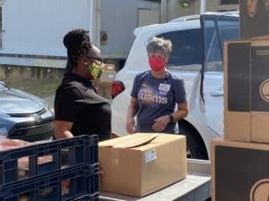 Stocked & Reddie volunteers Katriel Alexander (left) and Margaret Pauly put groceries in a vehicle. The food pantry changed to a drive-thru operation at the beginning of the COVID-19 pandemic.