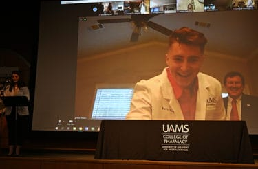 First-year pharmacy student Barry Powers smiles after donning his white coat and reaches down to turn off his camera for the Virtual White Coat Ceremony to proceed to the next student.