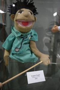 A surgeon hand puppet, with a stick for the puppeteer to control the arm.