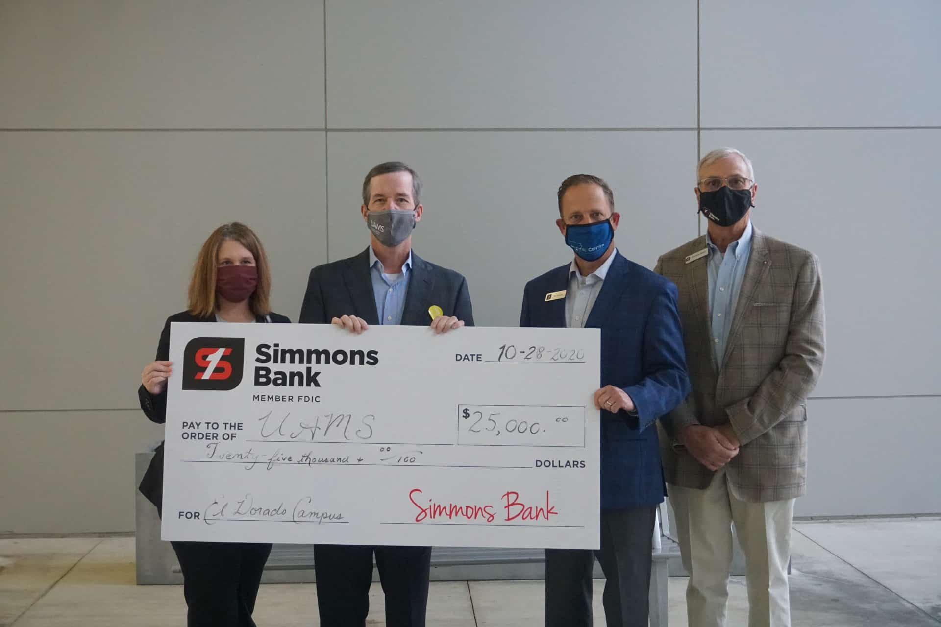 "UAMS Chancellor Cam Patterson, M.D., MBA, holds the $25,000 check with Amy Wenger, M.H.S.A., vice chancellor for Regional Campuses and Robert ""Rob"" Robinson, community president for Simmons Bank El Dorado. To their right is Freddie Black, chief business development officer for Simmons Bank."