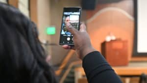 Ava Coleman, of the College of Nursing, snaps a photo as Patricia Cowan, Ph.D., RN, addresses the assembled faculty and  nursing students attending remotely.