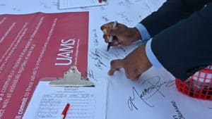 Brian Gittens, Ed.D., vice chancellor for diversity, equity and inclusion, signs his name to the banner.