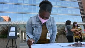 Alice Gardner, a student in the College of Public Health, signs the banner on Wednesday, Oct. 21.