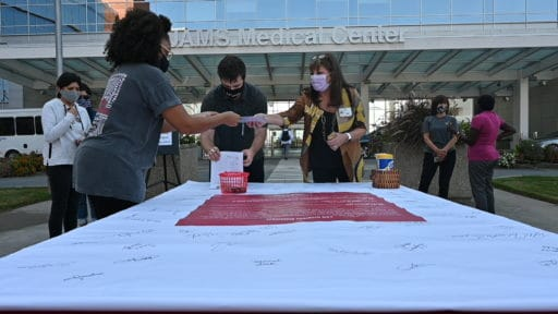 Students from the colleges of Public Health and Health Professions sign the diversity pledge banner, while faculty and staff greet them and help disinfect pens and markers.