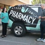 Megan Smith, left, talks to Brandon Achor on Oct. 1 outside Achor Family Pharmacy in Maumelle. Oct. 1 was the official launch date for the Flip the Pharmacy program in Arkansas.