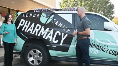 Megan Smith, left, talks to Brandon Achor on Oct. 1 outside Achor Family Pharmacy in Maumelle. Oct. 1 was the official launch date for the Flip the Pharmacy program in Arkansas.