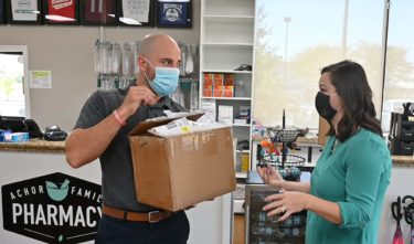 Achor, left, receives a box of Flip the Pharmacy materials from Smith at his Maumelle pharmacy.