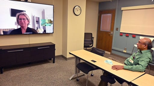 Hari Eswaran, right, uses a live video connection at the UAMS Institute for Digital Health & Innovation to talk with Mellie Bridewell, executive director of the Arkansas Rural Health Partnership.