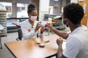 Students Natasha Wilbon and Rick Nouketcheussi practice how to show a patient the proper way to use an inhaler.