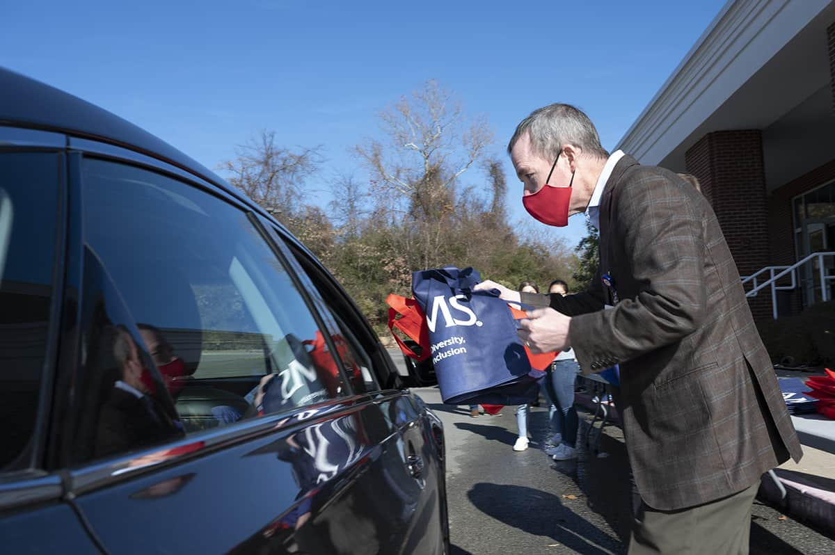 UAMS Chancellor Cam Patterson hands a large tote bag containing masks, hand sanitizer and bilingual information on Covid-19 during a drive-thru event Dec. 22 at Second Baptist Church in Little Rock.