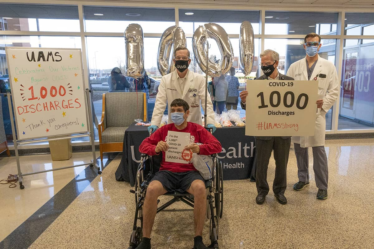 Michael Kent, seated left, holds a sign announcing he is the 1,000th COVID-19 patient to be discharged by the UAMS Medical Center. Behind Kent, left to right, are UAMS Chancellor Cam Patterson, UAMS Medical Center CEO Steppe Mette and hospitalist Franklin Gray.