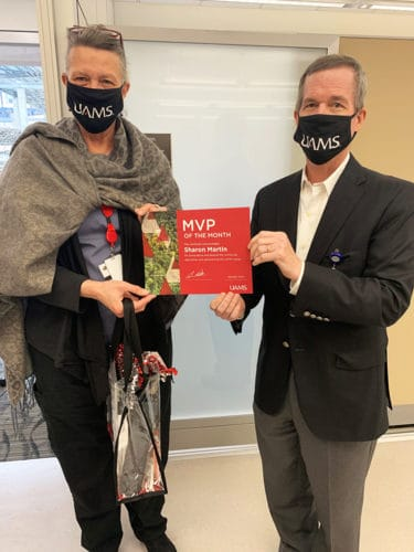 Sharon Martin, left, minutes after being surprised by UAMS Chancellor Cam Patterson, M.D., MBA, who presented to her the MVP award for January.
