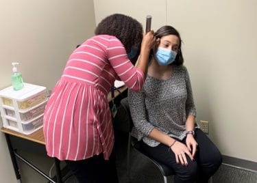 Students in the new Speech and Hearing Clinic location practice conducting ear examinations.