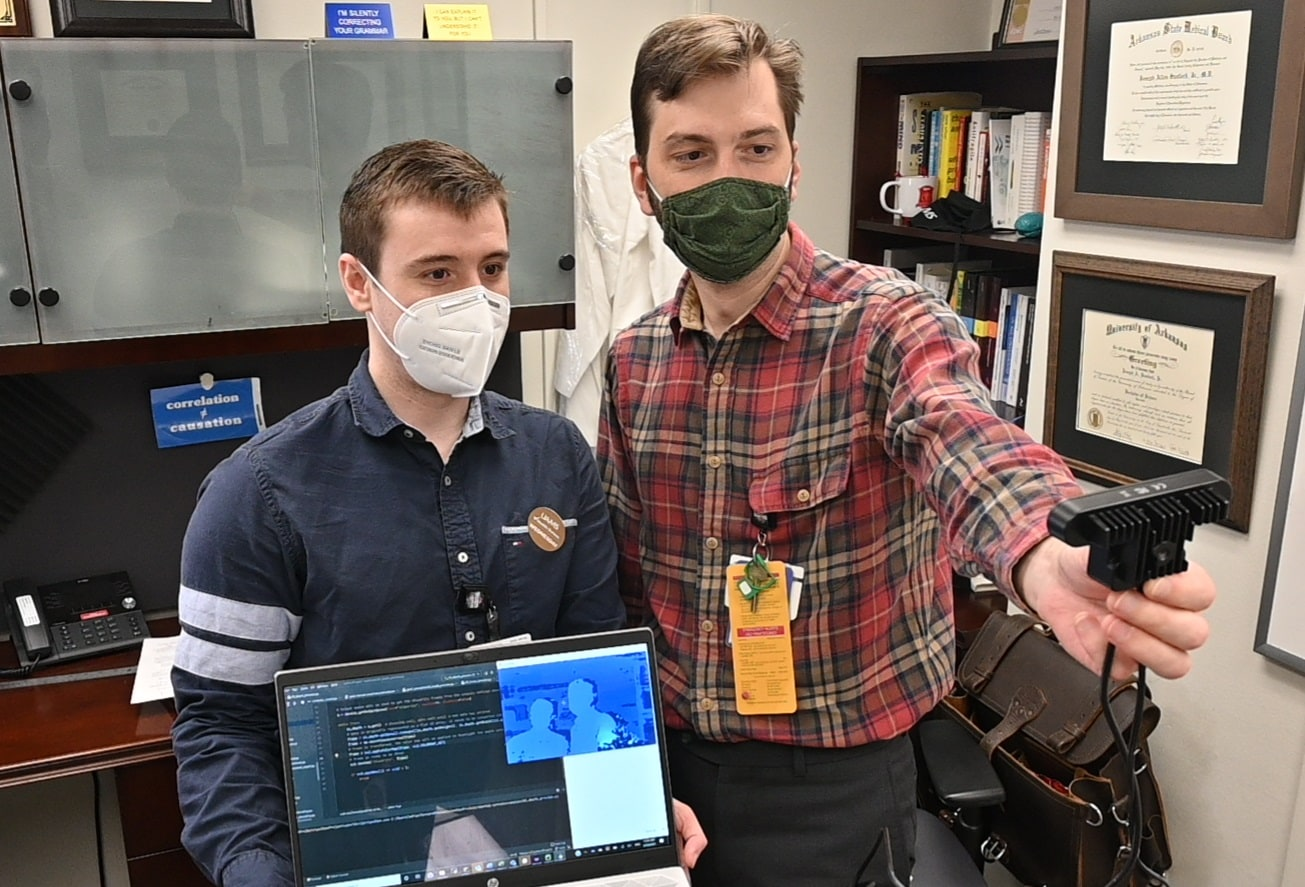 Joseph Sanford, M.D., and Adria Abella Villafranca use code they have written to test the OAK-D camera, equipped with spatial artificial intelligence.