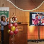 Madison Morris celebrates with family onscreen while Sharanda Williams and Sara Tariq, M.D., watch from the podium in the auditorium.
