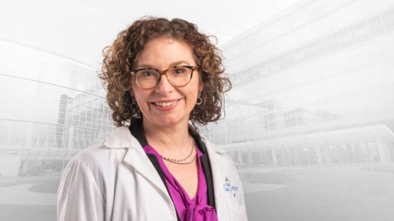 Sara Shalin, M.D., wearing white coat over business attire.