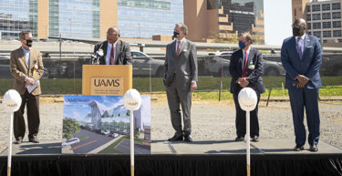 Chancellor Patterson, left, listens as Stephen Broughton, M.D., speaks. U.S. Rep. French Hill, C. Lowry Barnes, M.D., and Little Rock Mayor Frank Scott also spoke before the groundbreaking.