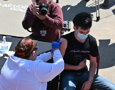 Tristan Taylor, 16, receives his COVID-19 vaccination at Simmons Bank Arena in North Little Rock. Teens as young as 16 recently were made eligible for the vaccine.
