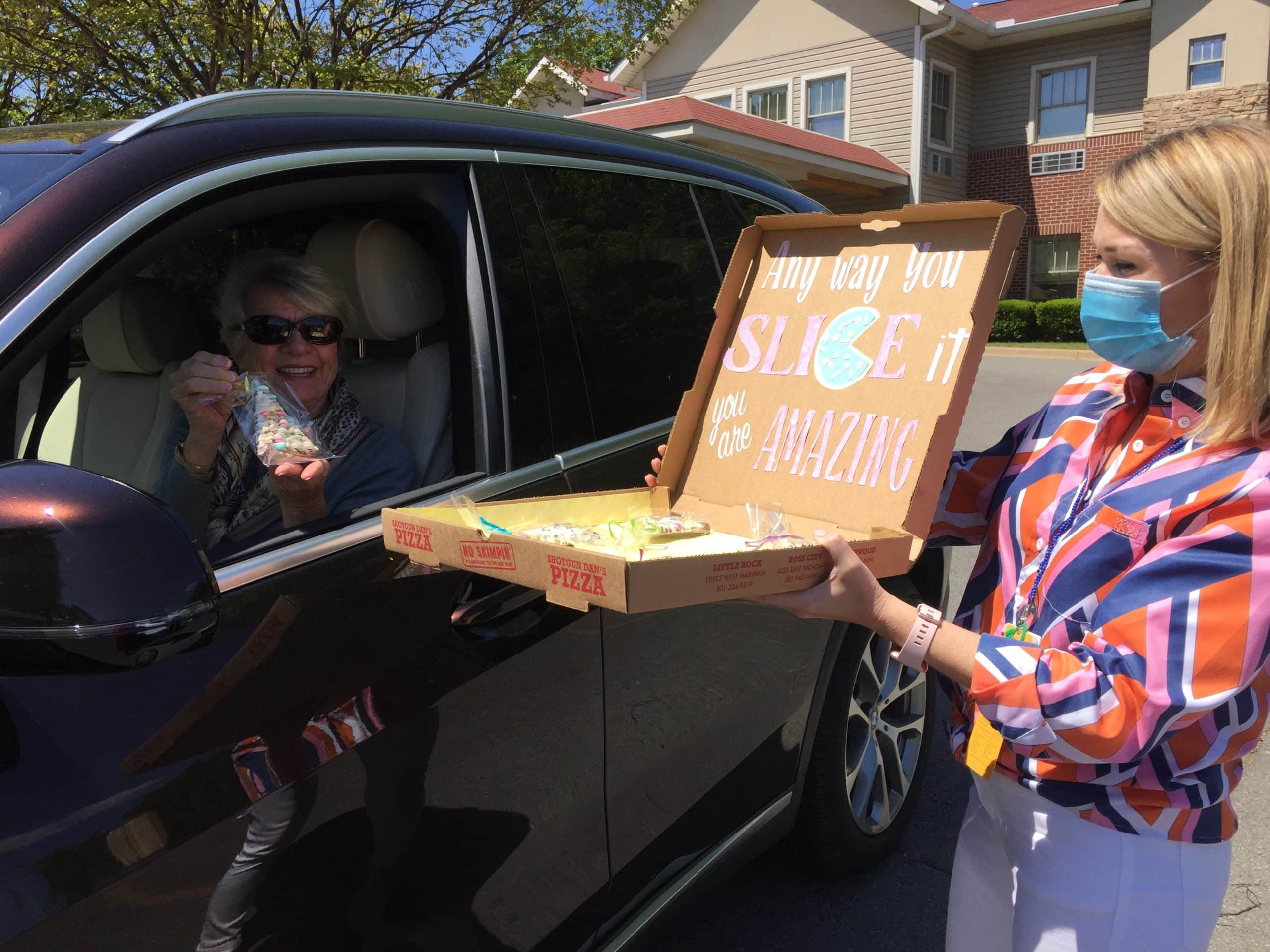 Stuart Cobb, a myeloma survivor who volunteers with the Winthrop P. Rockefeller Cancer Institute and serves on its board of advisors, picks up a sweet thank-you from Julia Hamra of the Cancer Institute's Volunteer Services and Auxiliary department during a recent appreciation drive-thru event for the institute's nearly 70 volunteers.