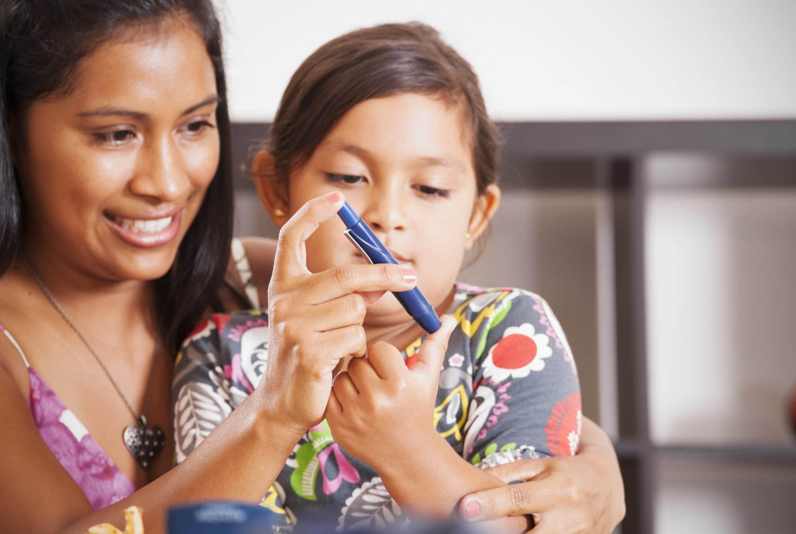 A mother helping her diabetic child monitor her blood sugar. Diabetes mellitus type 1, Juvenile diabetes.
