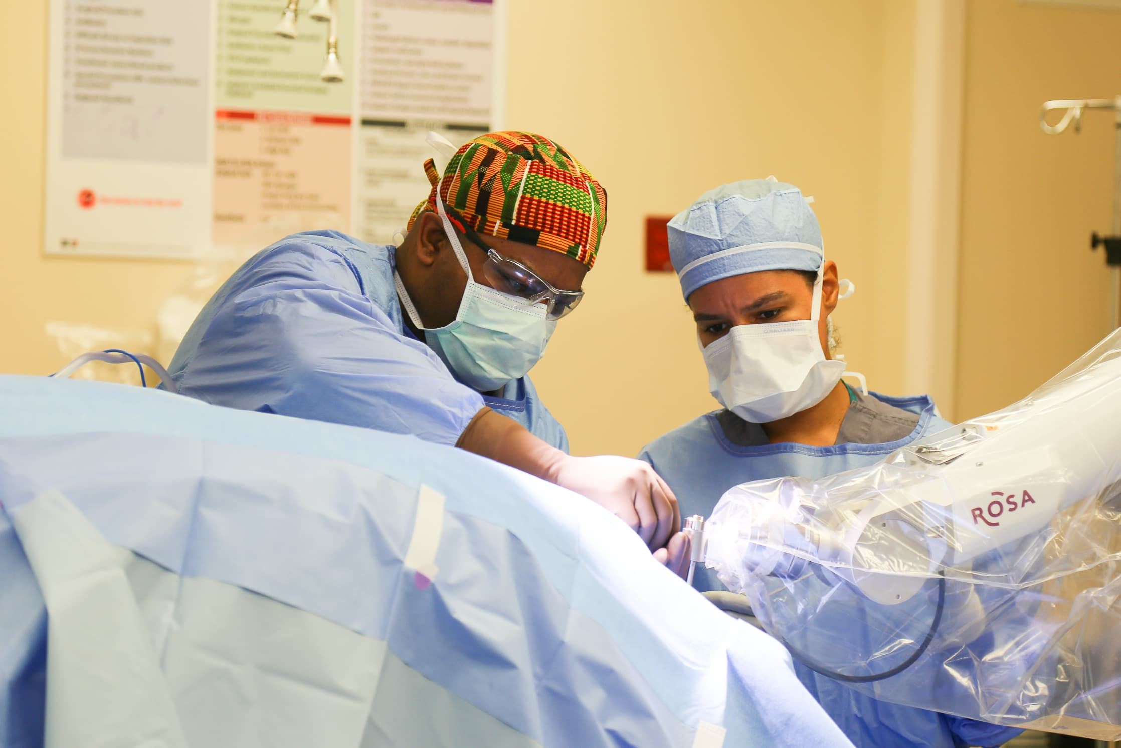 Analiz Rodriguez, M.D., Ph.D., and neurosurgical resident Marcus Stephens, M.D. perform surgery.