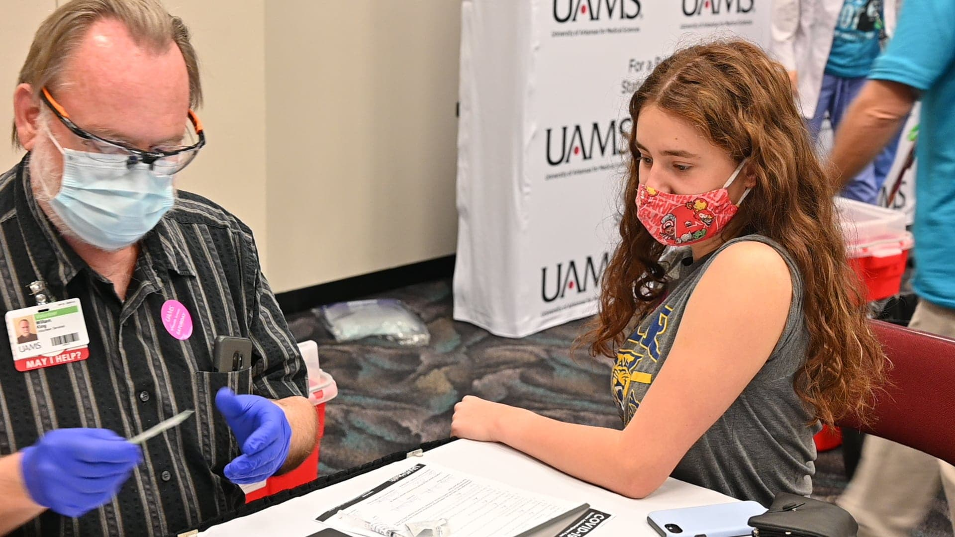 Ainsley Albright, 17, gets her first dose of the Pfizer vaccine at a COVID-19 Community Vaccination Clinic on April 10. Starting Thursday, UAMS will offer the vaccine to children ages 12 and up.