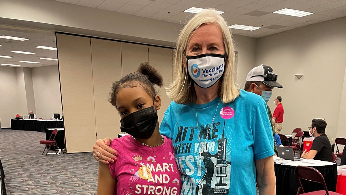 Chloe Pettus, 12, gets a hug from Margaret Powell, director of external affairs for the city of North Little Rock, after receiving her vaccination at Simmons Bank Arena.