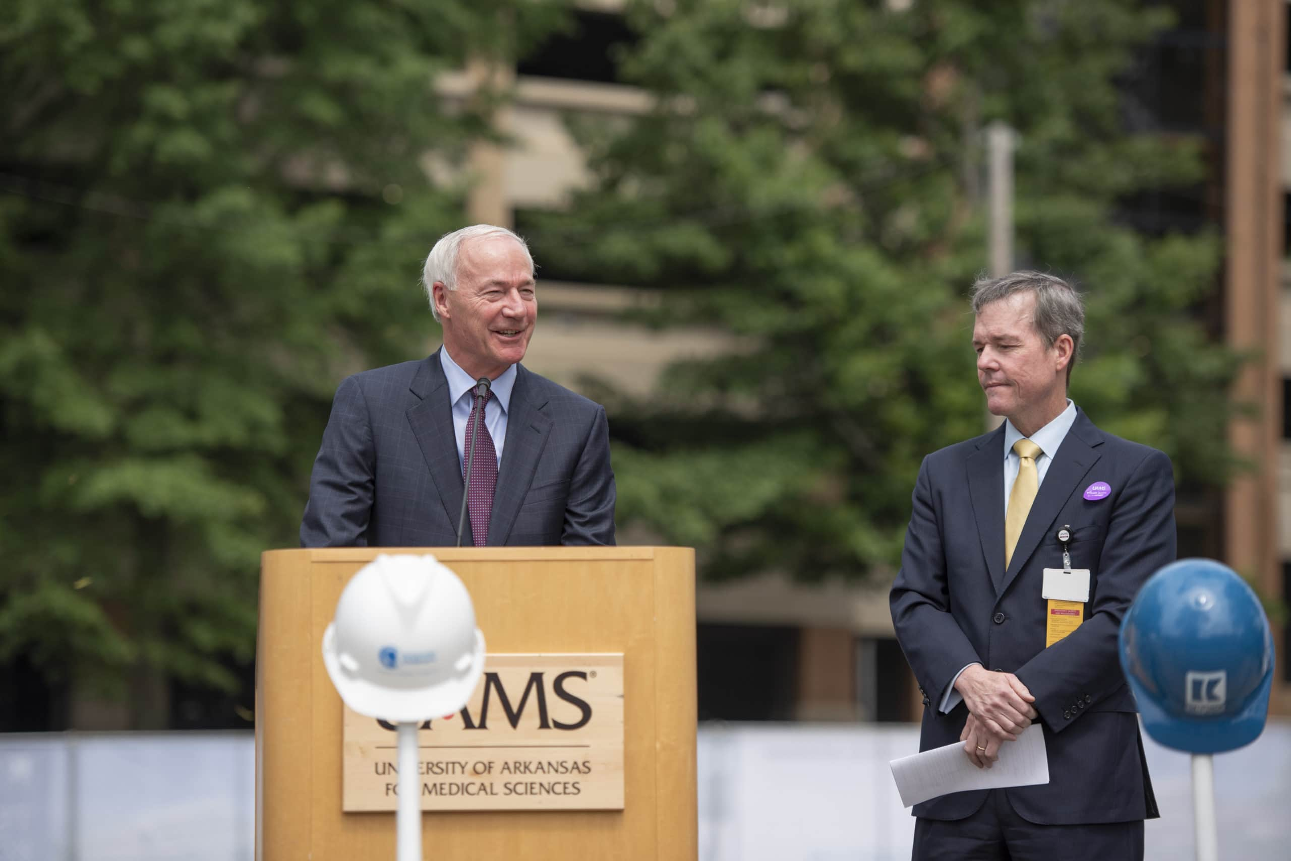 Gov. Asa Hutchinson speaks Tuesday at the groundbreaking ceremony for the UAMS Radiation Oncology Center as UAMS Chancellor Cam Patterson, M.D., MBA, looks on. The expanded Radiation Oncology Center will house Arkansas' first Proton Center, a partnership between UAMS, Baptist Health, Arkansas Children's and Proton International.