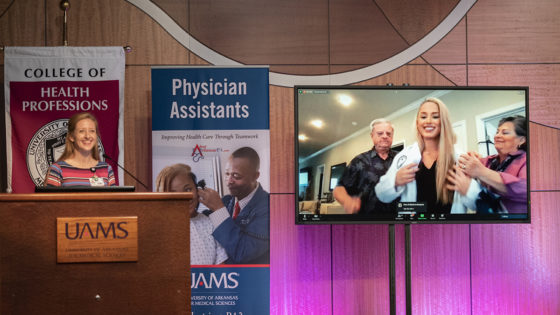 Tiffany Huitt, Ph.D., left, reads off the names of the 40 members of the Physician Assistant Class of 2023 as each in turn puts on their white coat during a partly virtual white coat ceremony.