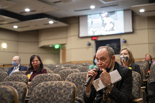 Michael Birrer answers an online question while seated with the other speakers and officials attending the Town Hall in Smith Auditorium. Unless speaking, all participants were masked and socially distanced.