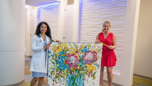 """Gwendolyn Bryant-Smith, M.D., director of the Breast Center at the Winthrop P. Rockefeller Cancer Institute and Natalie Rockefeller, who serves on the institute's board of directors, prepare to see """"Hope Blooms"""" by local artist Morgan Coven Herndon hung as one of the first three of several works are displayed in the center."""