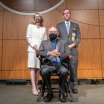UAMS Executive Vice Chancellor and College of Medicine Dean Susan Smyth, M.D., and UAMS Chancellor Cam Patterson, M.D., MBA, present Birrer (seated) with his commemorative medallion and inscribed wooden chair.