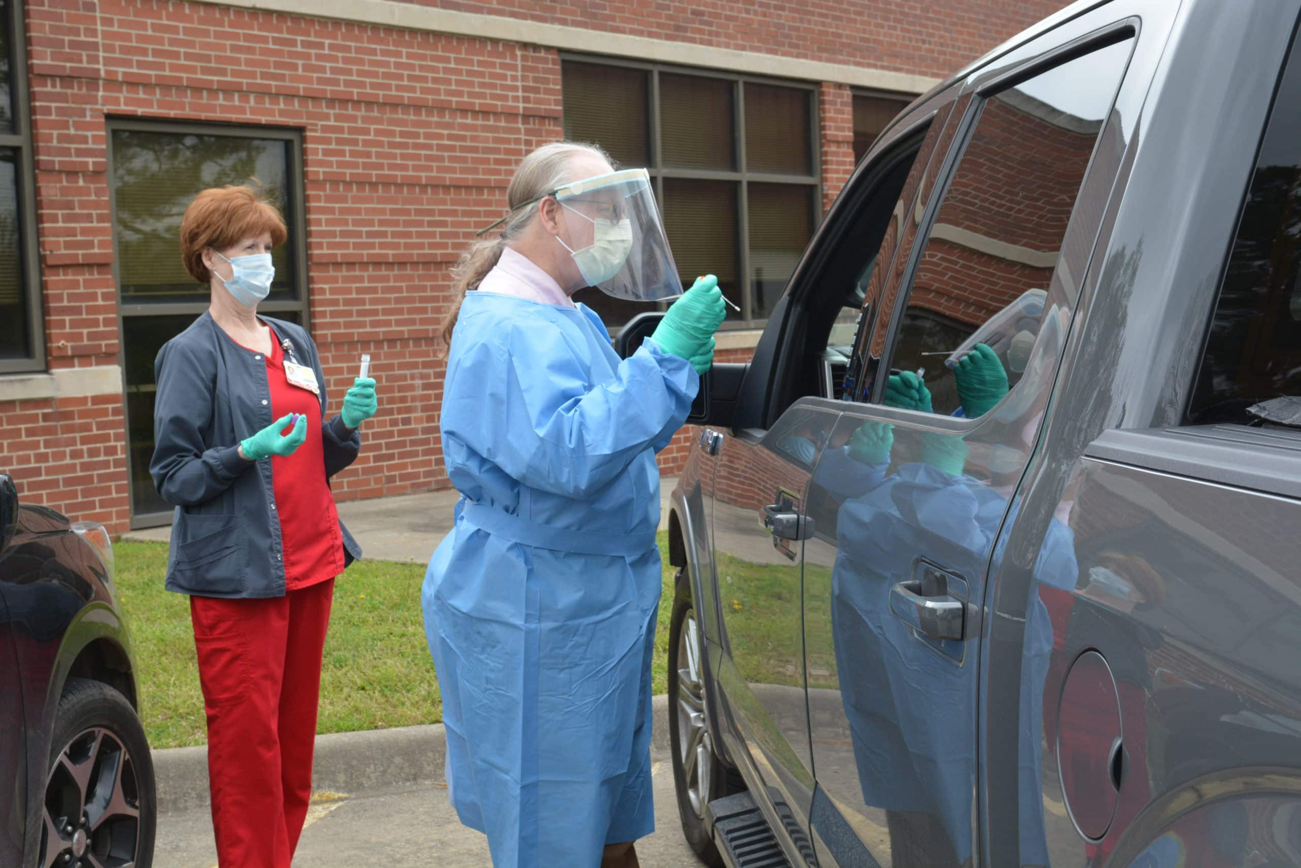 Ronald Brimberry, M.D., administers a COVID-19 test at a drive-thru testing site at the UAMS Northwest Regional Campus in Fayetteville.