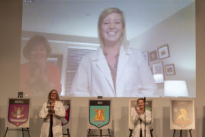 """Kathleen """"Katie"""" Kinder is helped into her white coat by her mother, as seen on a large screen in the auditorium."""