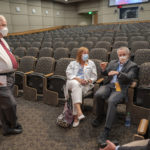 Before the town hall, Robert Hopkins Jr., second from right, talks with James Graham (standing), Michelle Krause and Steppe Mette, right. All four physicians made up a panel of experts who answered questions at the meeting.